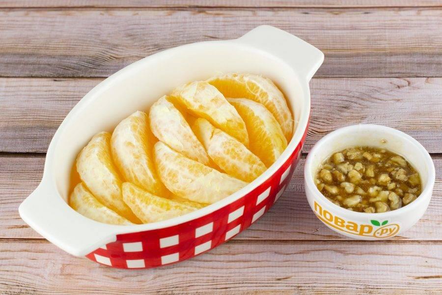Апельсины очистите от шкурки и белых пленок, разделите на дольки. Выложите дольки в форму для запекания. Орехи немного порубите. Мед перемешайте с корицей и орехами.