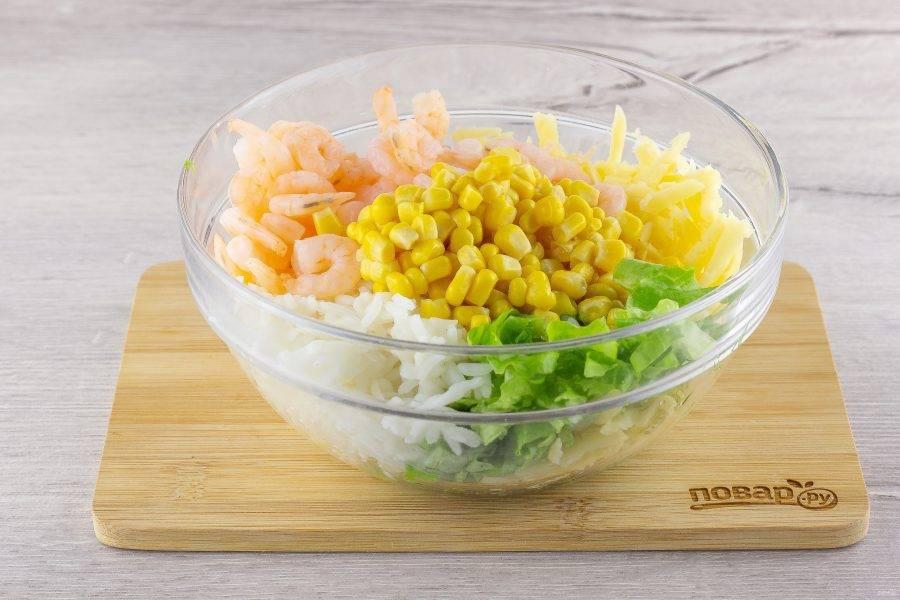 Немного риса отложите для украшения салата, а  остальные составляющие соедините в миске: рис, креветки, кукурузу, сыр и листья салата.