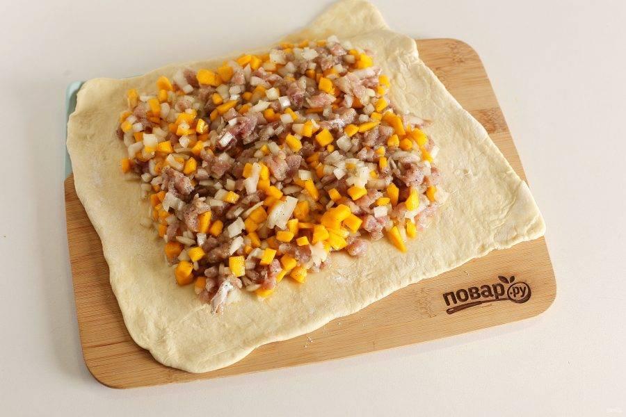 Рабочую поверхность посыпьте мукой и раскатайте тесто в тонкий пласт. В центр выложите начинку.