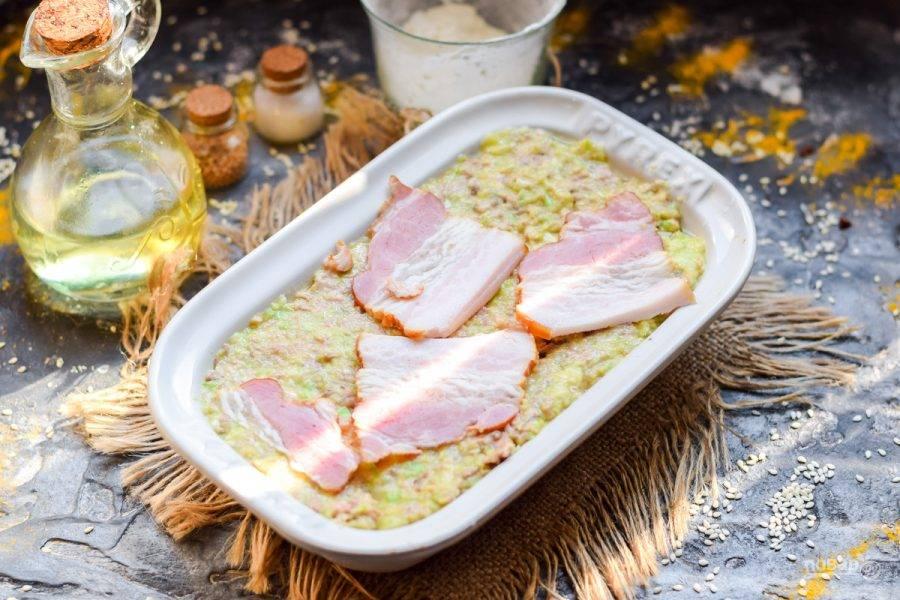 Форму для духовки смажьте маслом, выложите подготовленную массу. Поверх выложите немного бекона.