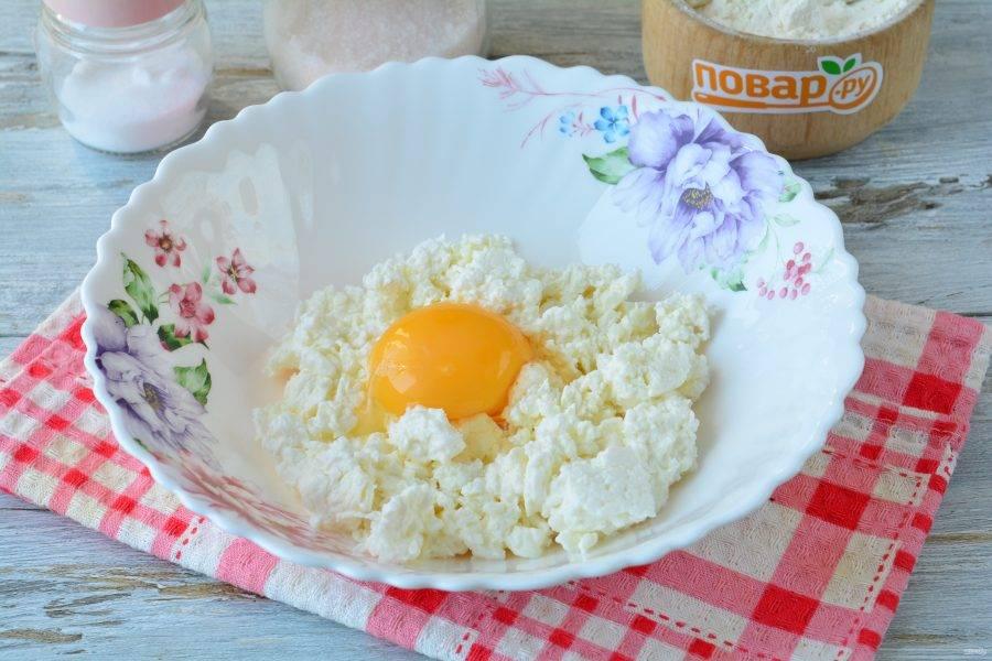 Всыпьте творог в глубокую миску, вбейте куриное яйцо.