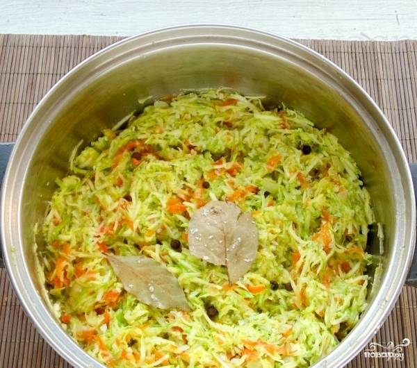 Добавьте кабачок к луку с морковью. Тушите, помешивая, несколько минут до выделения сока. Затем добавьте перец, соль, лавровый лист и сахар.