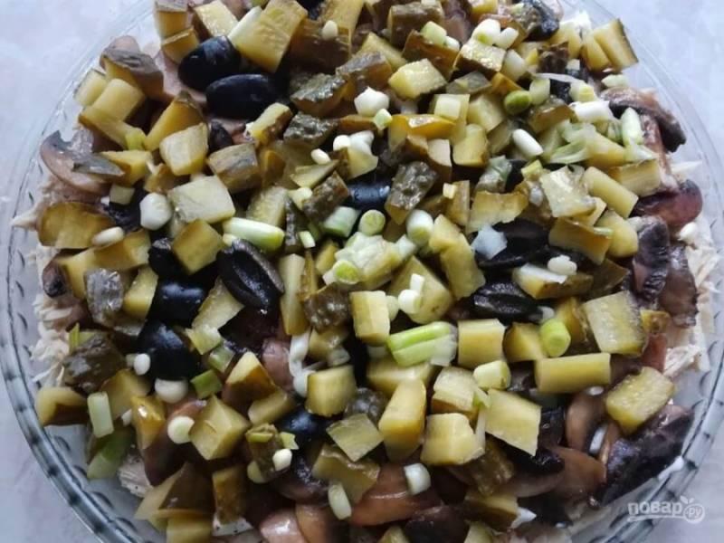 3.Нарезаю маринованные огурцы кубиком, маслины разрезаю на 2-3 части. Мою и нарезаю зеленый лук, перемешиваю измельченные ингредиенты (немного лука оставляю для украшения), выкладываю поверх грибов.