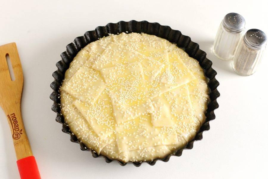 Смажьте пирог желтком и посыпьте кунжутом. Выпекайте в духовке при температуре 190-200 градусов 30-40 минут до румяного цвета.