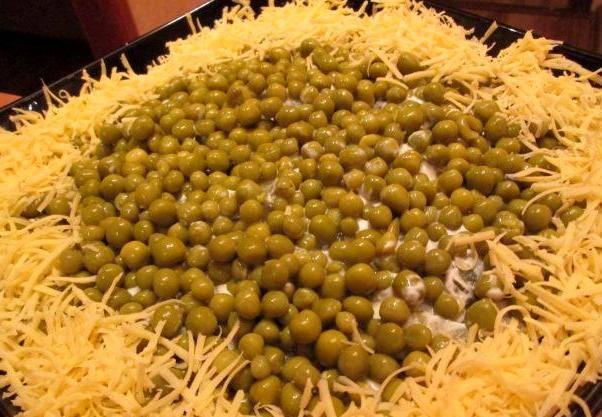 Теперь идет слой из консервированного зеленого горошка, он будет последним. Нам остается только украсить салат по бокам тертым сыром и подать к столу. Приятного аппетита!