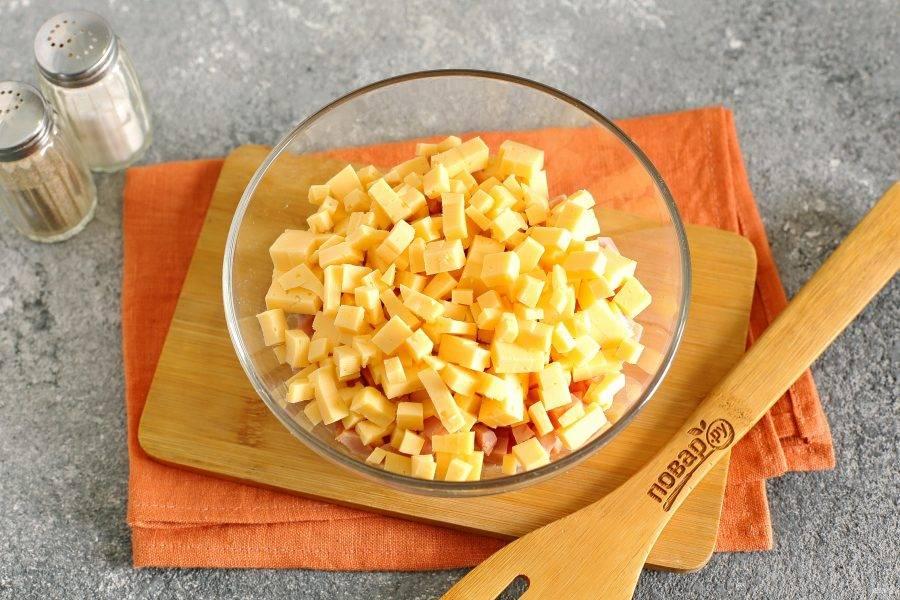 Добавьте нарезанный кубиками сыр.