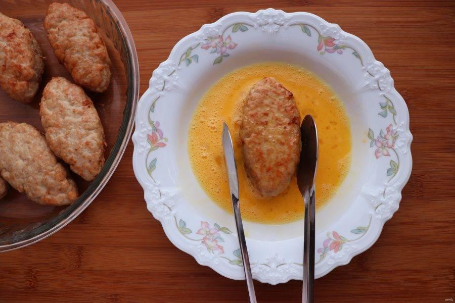 Обжарьте котлеты на растительном масле по 2 минуты с каждой стороны. Жарьте котлеты небольшими порциями, чтобы они не выпустили сок. Взбейте яйцо. Обмакните каждую котлету во взбитое яйцо и выложите в жаропрочную форму, смазанную маслом.