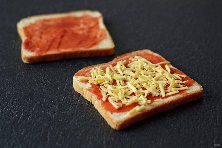 Сыр натрите на крупной терке. Добавьте его на одну половинку хлеба.