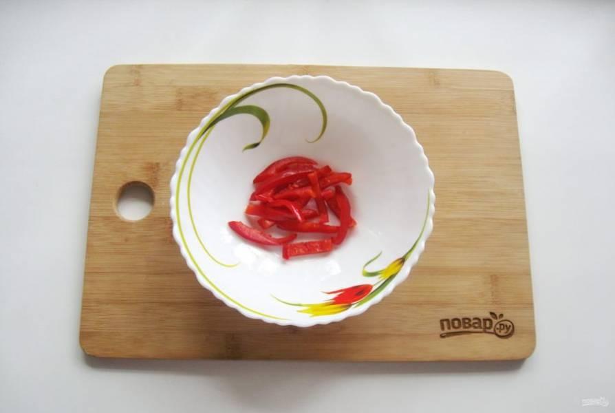 Болгарский перец очистите и помойте, нарежьте соломкой и выложите в салатник.