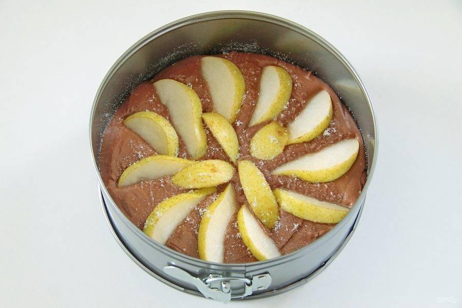 5. Переложите тесто в смазанную маслом форму. Дно и бока по желанию присыпьте манкой. Сверху равномерно распределите нарезанную дольками грушу, слегка вдавливая ее в тесто и присыпьте сахаром.