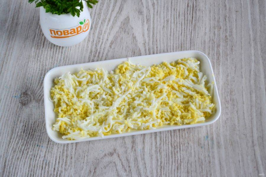 Яйца очистите от скорлупы. Одно яйцо натрите на терке и выложите первым слоем на плоскую тарелку. Сверху слегка смажьте майонезом.