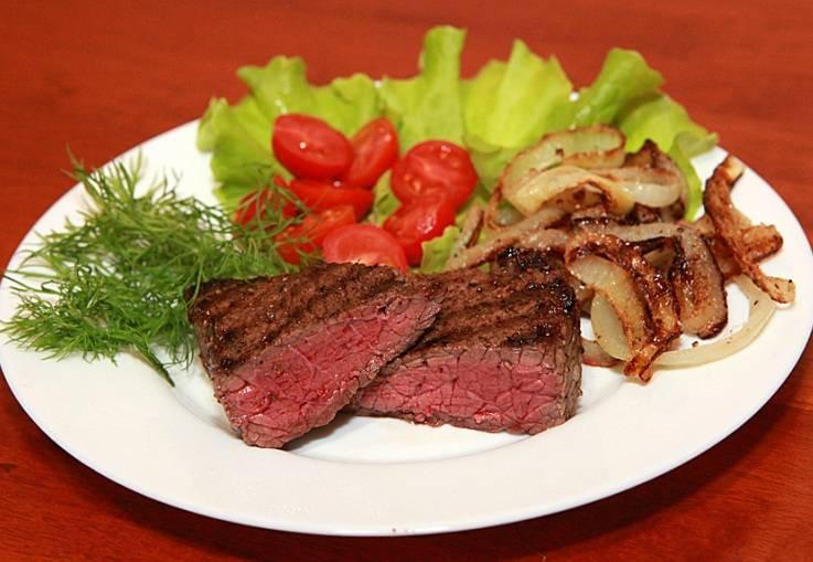 Теперь подаем стейки из говядины с обжаренным луком на гарнир и с солонкой, солить мясо нужно непосредственно во время еды. Приятного всем аппетита!