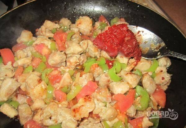 Потом добавьте на огонь нарезанный помидор и пасту. Всё перемешайте.