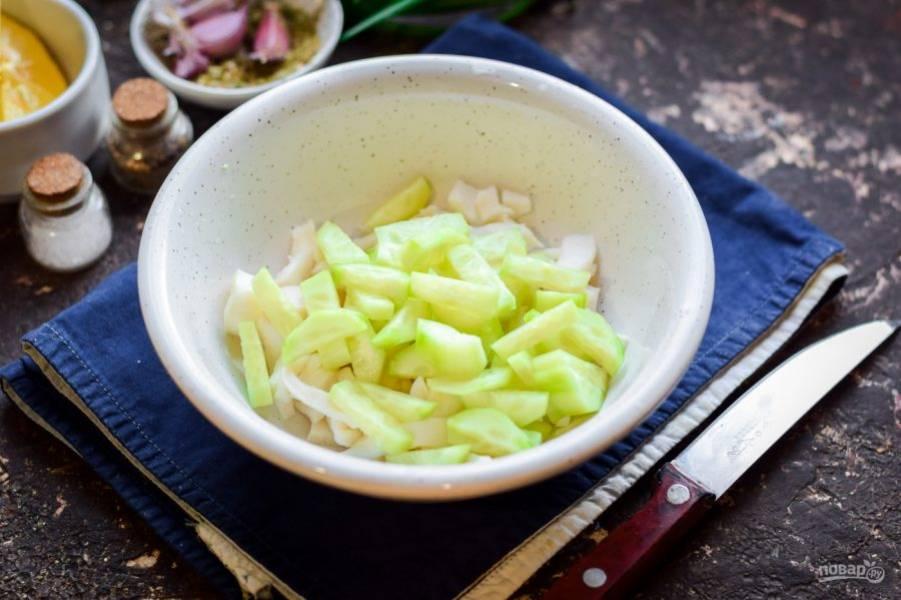 Свежий огурец очистите от кожуры, после сполосните. Нарежьте огурец небольшими полосками и добавьте к кальмарам.