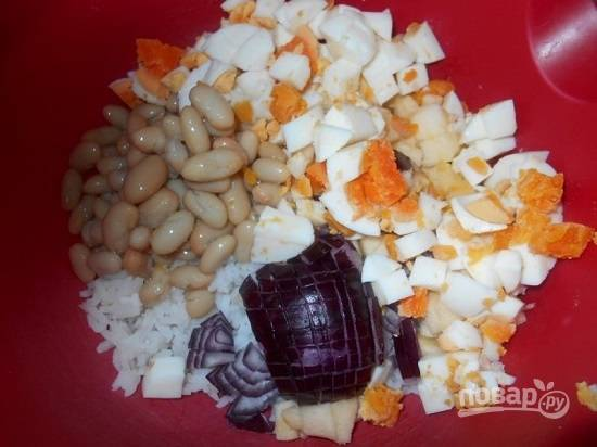 Очистим лук и яблоко. Нарезаем лук, яблоко и яйца кубиками. Добавляем консервированную фасоль.