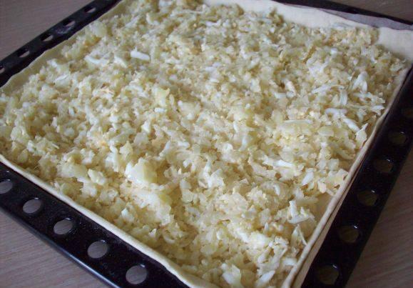 Тесто раскатываем по форме противня. Делаем в тесте бортики по краям, чтобы начинка не выпадала. Начиняем пирог яйцами с капустой.
