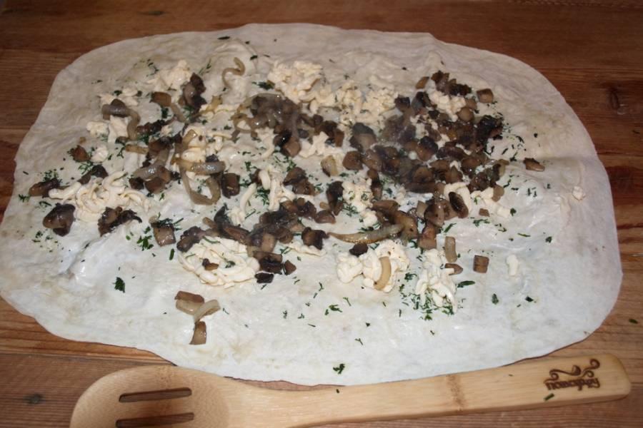 На терке натрите плавленый сырок. Распределите его по всему лавашу. Измельчите зелень. Обжаренные грибы выложите поверх всего.