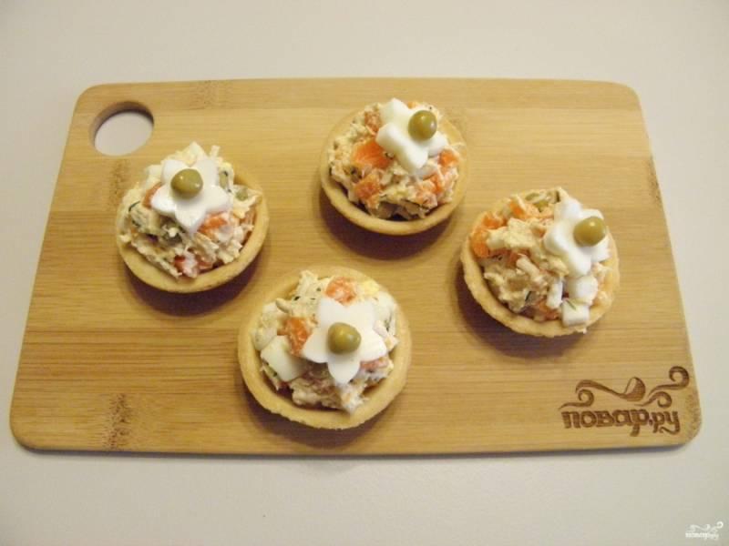 Разложите салат по тарталеткам. Украсьте цветочками из белка и горошин. Приятного аппетита!