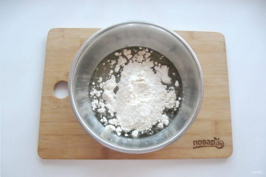 Добавьте соль и постепенно всыпьте муку.