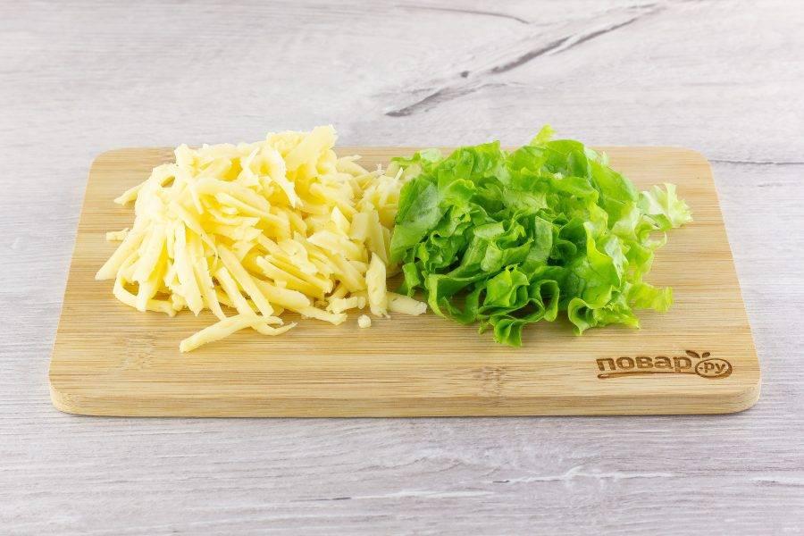 Листья салата помойте, обсушите и нарежьте. Сыр натрите на крупной терке.