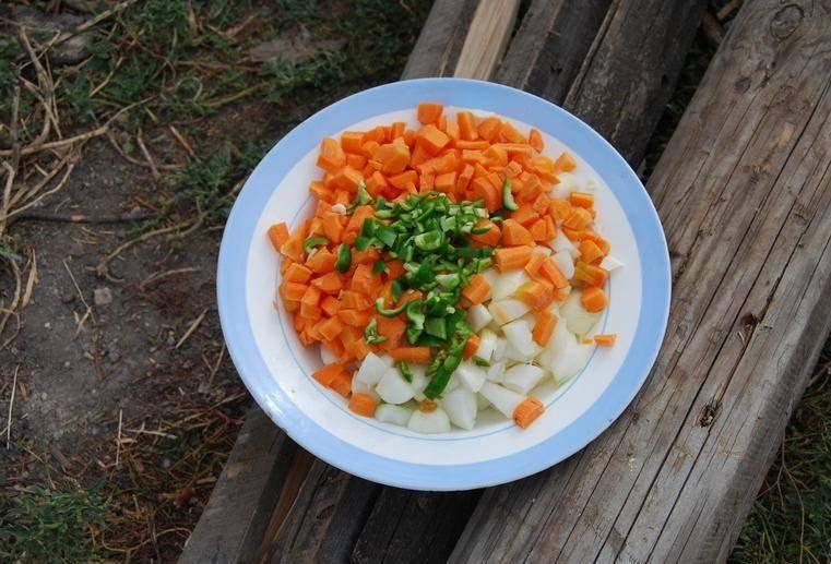 2. Когда мясо покроется корочкой - добавим измельченные лук, морковку и перчик.