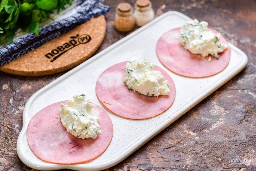 Ветчину нарежьте максимально тонкими пластинами, выложите на ветчину по ложке творожного сыра.