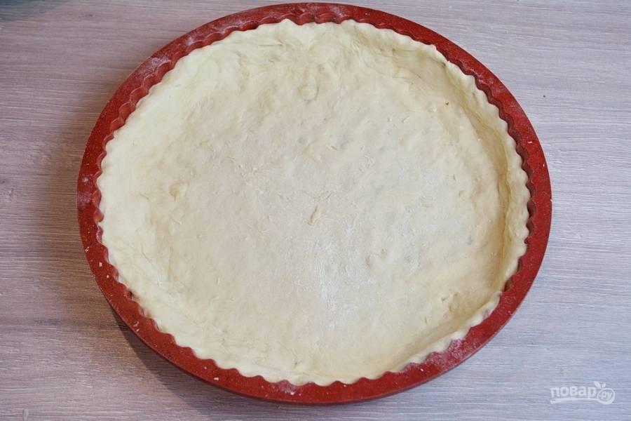 Подошедшее тесто нужно обмять. Добавьте 50-70 граммов муки, раскатайте и уложите в форму. Лишнее тесто обрежьте.