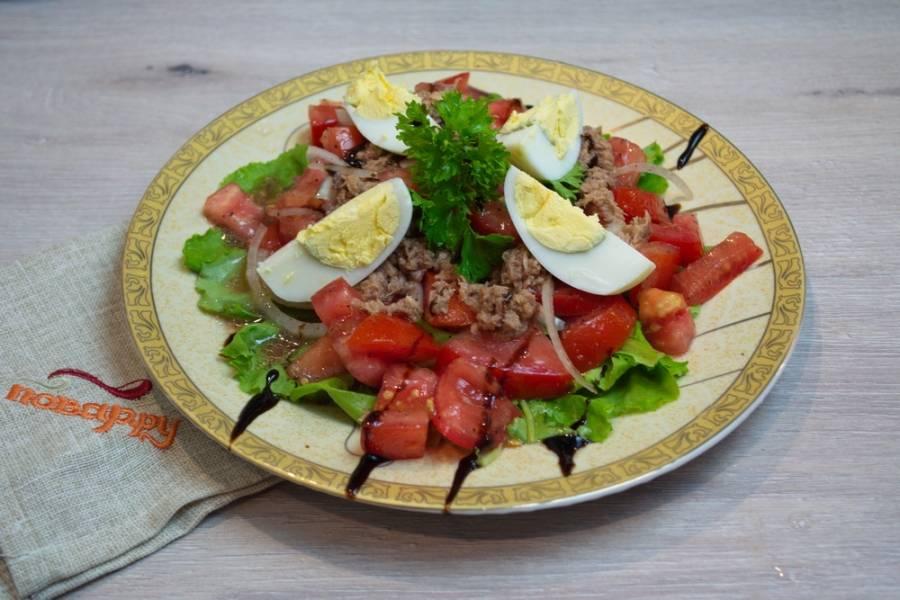 На листья салата выложите помидоры с луком. Сверху на помидоры выложите консервированного тунца. Он уже с маслом. Масло аккуратно сдобрит сам салат. Наверх положите отваренные яйца.