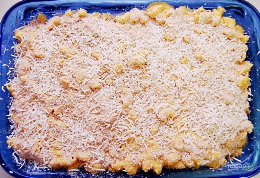 4. Теперь выложите макароны в форму для выпечки. Сверху распределите оставшееся масло. Влейте молочный соус. Натрите сыр. Всыпьте красный перец и сухари.