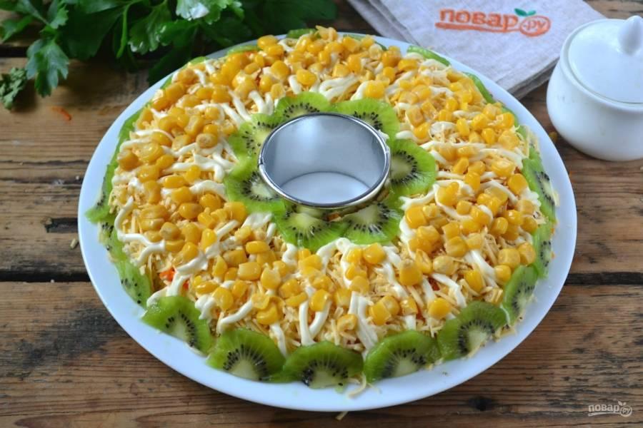 Сверху украсьте салат тонкими пластинами киви и кукурузой, как на фото. Получится очень нарядно и празднично. Кушайте с удовольствием!