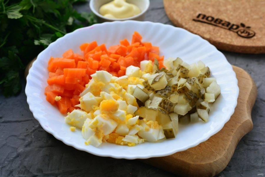 Нарежьте кубиками отварную морковку, яйца и соленые огурцы.