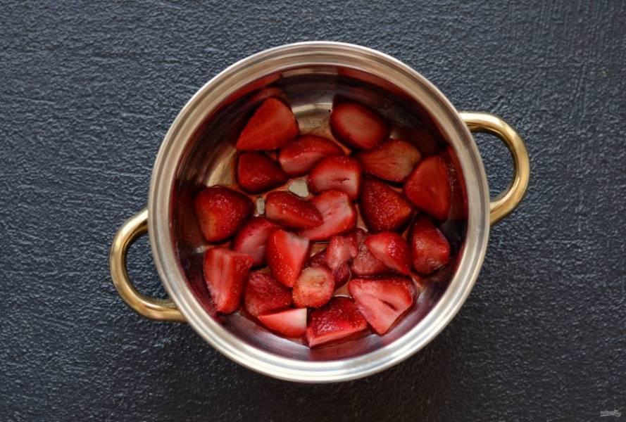 Клубнику разрежьте на половинки или четвертинки. Переложите клубнику в кастрюлю с водой, добавьте сахар.
