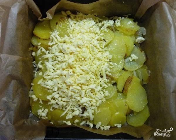 Обжаренный картофель перекладываем в жаропрочную емкость, подложив пергаментную бумагу. Трем на терке сыр и посыпаем им картошку.