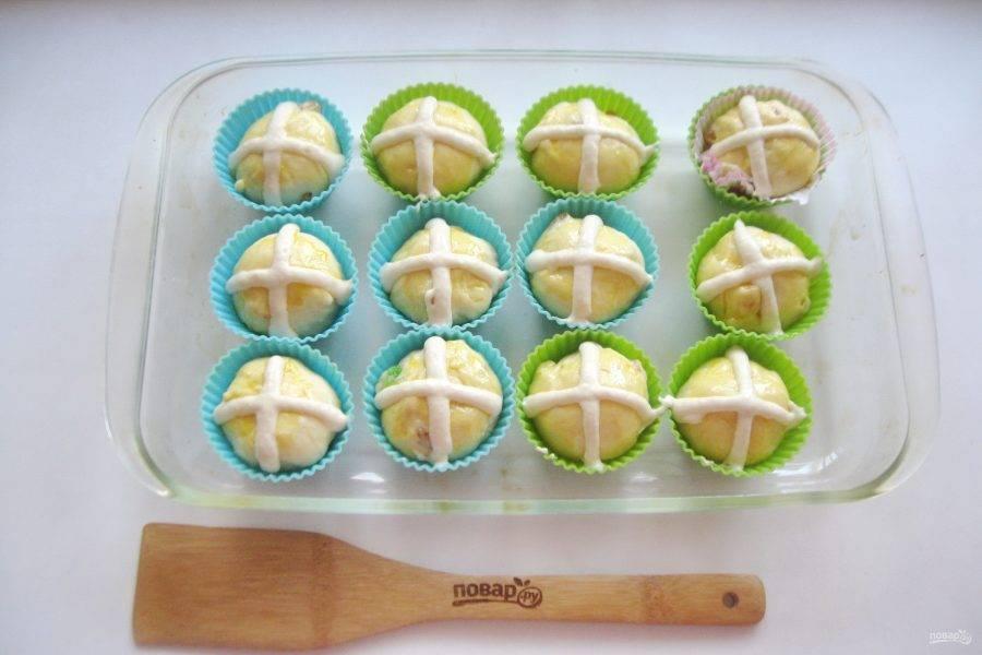 Булочки смажьте яйцом. Сверху с помощью кулинарного мешка приготовленным тестом нанесите крест.