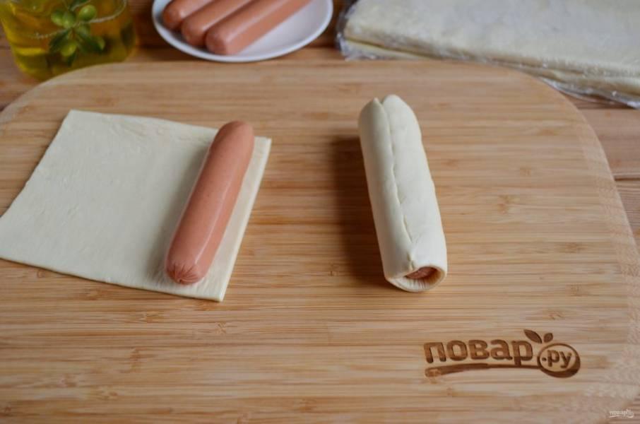 Разверните тесто, обычно получается 4 листа длинных. Каждый кусочек теста порежьте на половинки, чтобы получились небольшие квадраты. На край каждого квадрата положите по сосиске и сверните в рулет. Край плотно защипните.