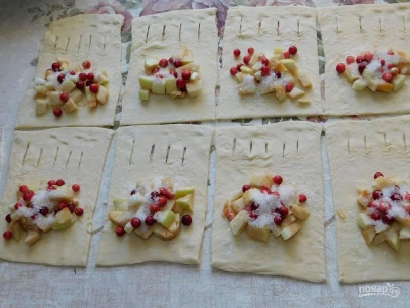 На одной половине каждого кусочка теста сделайте небольшие надрезы. На другую выложите немного нарезанных яблок и бруснику. Посыпьте сахаром.