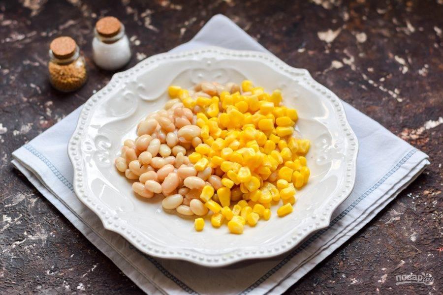 Консервированную фасоль промойте и переложите в тарелку. Откройте кукурузу, сок слейте, добавьте кукурузу к фасоли.