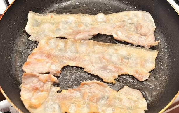 Уложите на хлеб поджаренные ломтики бекона.