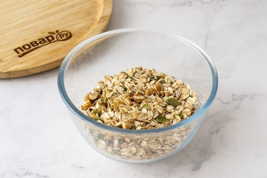 Переложите в глубокую миску овсяные хлопья. Добавьте грецкие орехи и тыквенные семечки, все перемешайте.