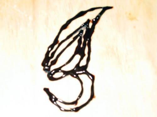 5. С помощью кондитерского шприца на пергаментной бумаге сформируйте крыло бабочки молочным шоколадом.