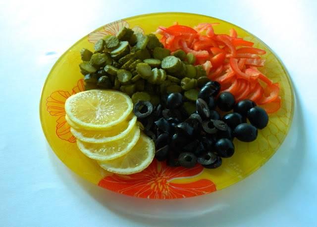 Нарезаем огурцы. Оливки или маслины можно разрезать пополам. Если они у вас с косточками - выберите косточки. Нарезаем лимон.