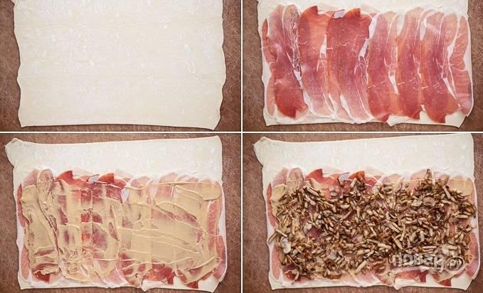 2. На рабочий стол выложите тесто, раскатайте. Распределите по тесту прошутто или бекон. Смажьте небольшим количеством горчицы и сверху выложите жареные грибочки.