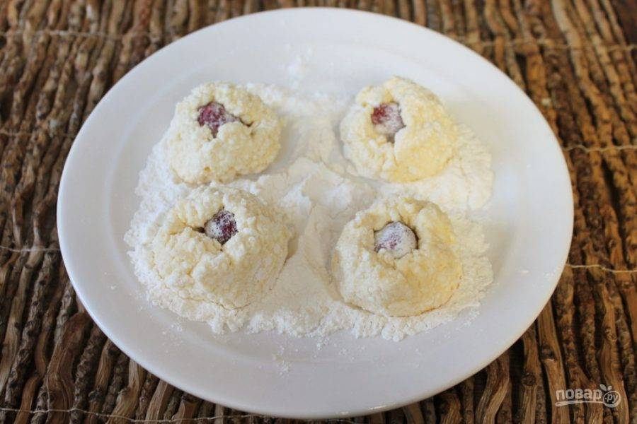 Из творожного теста формируем сырники, в средину каждого сырника кладем ягоду. Сырники обваливаем в муке.