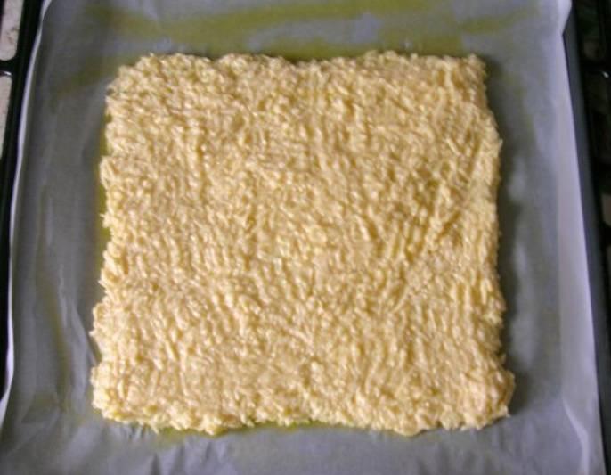 Застелите противень бумагой для выпечки, смажьте ее оливковым маслом. Выкладываем сырно-яичную начинку ровным слоем. Ставим запекаться в духовку на 5 минут, температура 180 градусов.