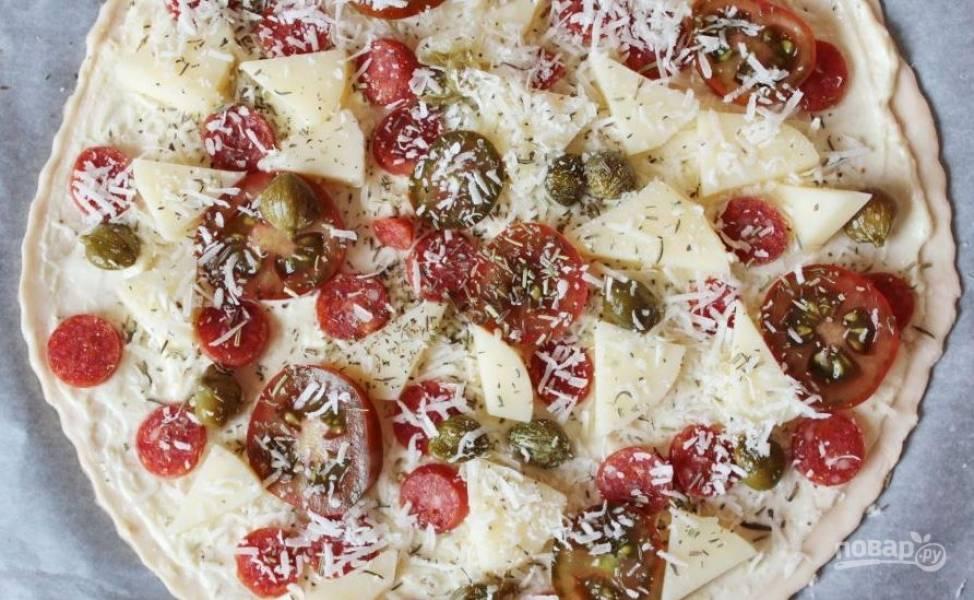 Колбасу нарежьте кружочками и выложите поверх соуса. Нарежьте оба вида сыра и помидоры черри, равномерно распределите ингредиенты на пицце. Посыпьте все тертым сыром, каперсами и сушеными травами. Запекайте пиццу в духовке при 200 градусах пятнадцать минут. Приятного аппетита!