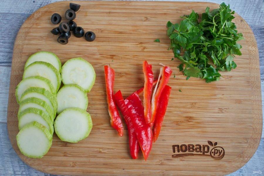 Кабачок нарежьте тонкими кружками, перец - тонкими полосками, маслины - колечками, зелень измельчите. Сложите нарезанные ингредиенты в миску, посолите, поперчите, полейте оливковым маслом, перемешайте.