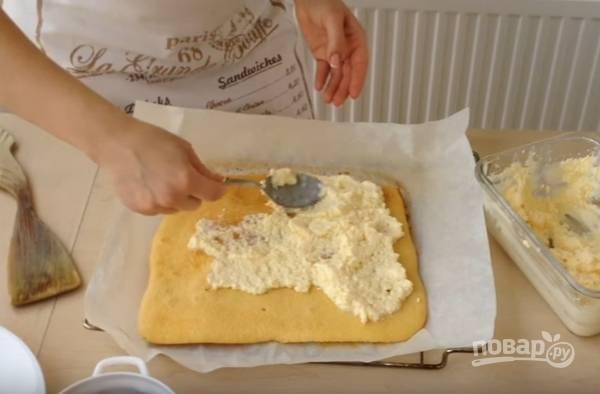 8.Достаньте противень с бисквитом, снимите последний вместе с пергаментом на полотенце. Немного остывший корж смажьте приготовленным кремом из сливочного масла и сгущенки, распределите по всей поверхности бананы.