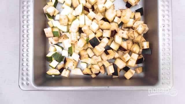 Баклажан и цуккини вымойте и порежьте некрупными кусочками. Выложите в форму для запекания.