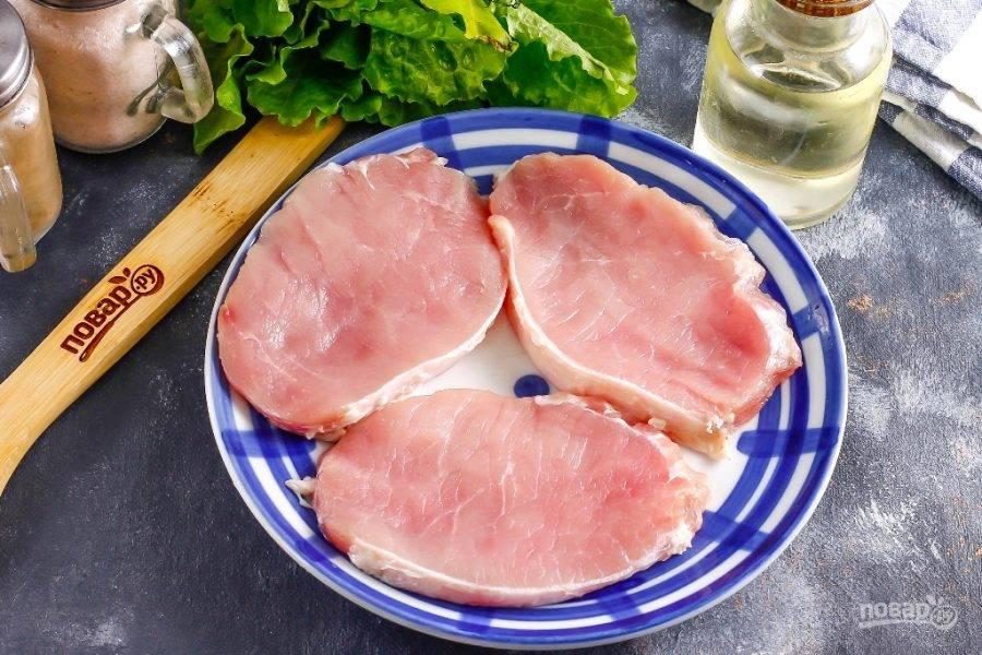 Мякоть свинины промойте в воде, срежьте с него жилы и пленки, но не срезайте белую пленку, которая сбоку держит весь кусок мяса. Благодаря ей ромштексы будут держать свою форму при обжаривании. Нарежьте мякоть порционными ломтиками толщиной не менее 1 см. Отбивать мясо не нужно — это не отбивные!