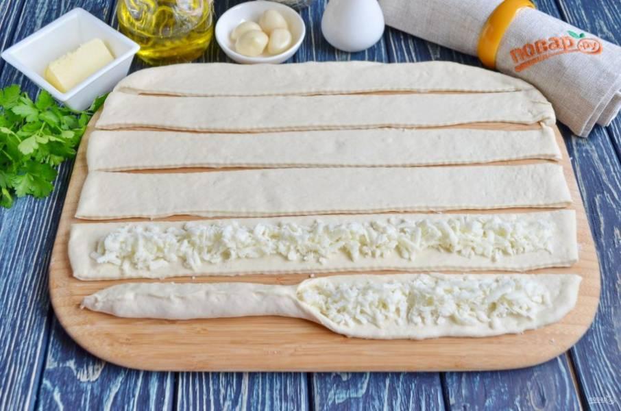 """Присыпьте стол мукой, раскатайте тесто в прямоугольник. Ножом для пиццы порежьте его на полоски, ширина и длина значения не имеет, как нравится, от этого будет зависит только размер узелков. На каждую полосочку теста положите """"дорожкой"""" сыр. Скрепите края."""